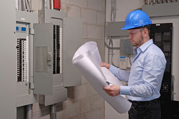 an electrical engineer reviewing electrical panel blueprints